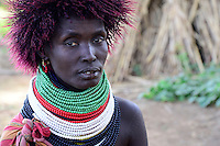 KENYA Turkana, Lodwar, Turkana village Kaitese, Turkana woman with wig infront of maize field, traditional the Turkanas a cattle holder but due to climate change the shift to farming too / KENIA Turkana, Lodwar, Dorf Kaitese, Turkana, eigentlich traditionell Viehhalter, beginnen mit Unterstuetzung von GIZ und Save the children ein Maisanbau Projekt zur Ernährungssicherung und Anpassung an den Klimawandel