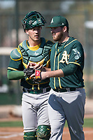 Oakland Athletics pitcher Corey Walter (57) talks to catcher Collin Theroux (55) during Spring Training Camp on February 24, 2018 at Lew Wolff Training Complex in Mesa, Arizona. (Zachary Lucy/Four Seam Images)