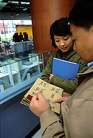 A real estate agent introduces room models to a potential customer at a show room in Beijing, China..