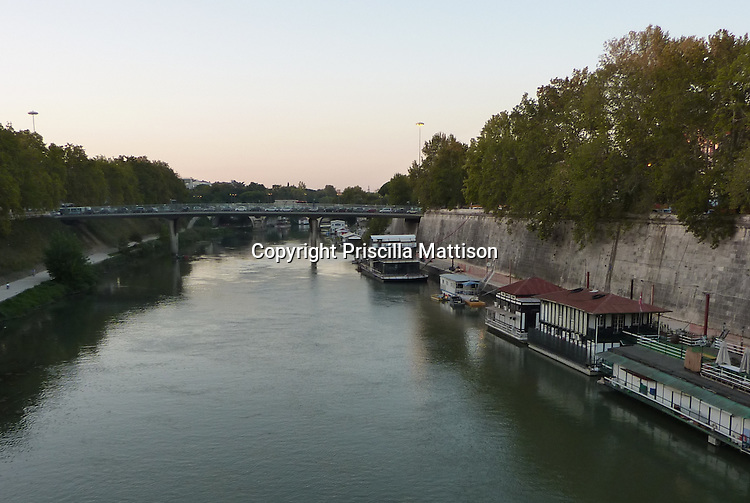 Rome, Italy - October 6, 2013:  Houseboats line the Tiber and cars  line a bridge.