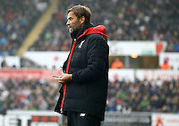 Liverpool manager Jurgen Klopp cleans his glasses from the rain on his under coat during the Barclays Premier League match between Swansea City and Liverpool played at the Liberty Stadium, Swansea on 1st May 2016