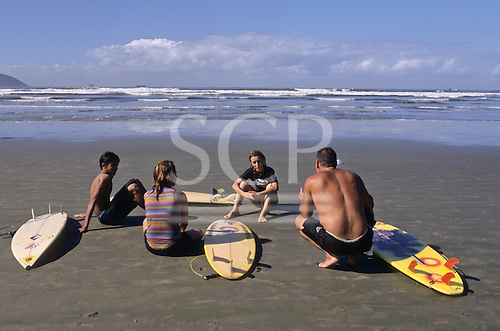 Southern Brazil. Instructor teaching a group of kids on the beach with their Malibu surf boards with waves in the sea.