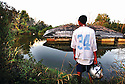 Maverick Ancar, a football player for Port Sulfur High School, looks at his home floating in a canal, 2006.