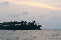 As the red sun drops quickly to the horizon in the tropics, a calm settles over Barberyn Island and its Light offshore of Beruwala, Sri Lanka