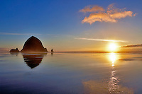 Low tide reflection with Haystack Rock and sunset. Cannon Beach. Oregon