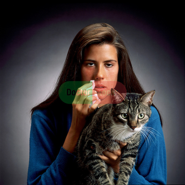 young woman with allergies on verge of sneezing while holding cat