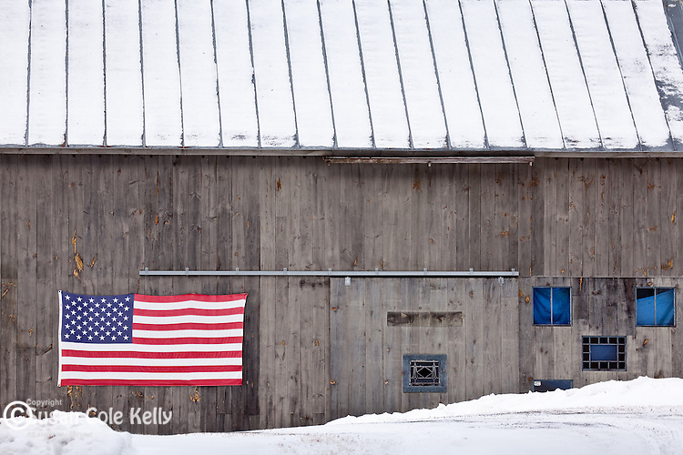 A gray barn with American flag and blue windows in Pomfret, near Woodstock, VT, USA