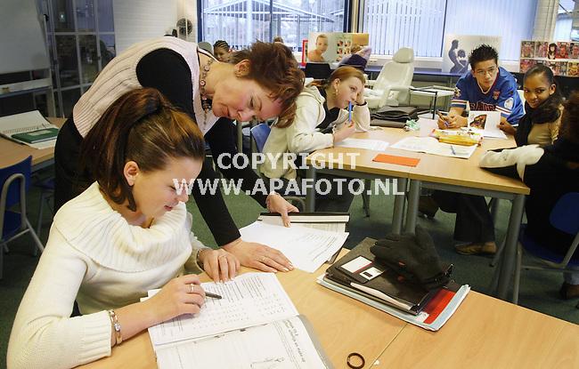 Nijmegen, 280103<br />Kandinsky College<br />Een docent geeft uitleg aan een leerling. Geen klassituatie in (o.a.) de afdeling verzorging van de school. De leerlingen zijn individueler bezig.<br />Foto: Sjef Prins - APA Foto
