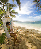 Young woman reading a book in a hammock at Sunset Beach, North Shore of Oahu