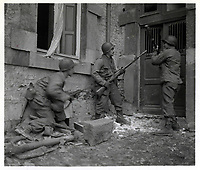 Three Americans of the 117th Infantry Regiment are about to enter a house where several enemy snipers are holding out. 24 December 1944<br /> <br /> <br />  The town where this action took place, is Stavelot, Belgium. The Germans broke through here and took the town, but U.S. forces effected a re-capture. 30th Infantry Division, 117th Regiment, Stavelot, Belgium.