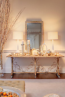A rustic table against one wall of the living room displays a collection of candles, candlesticks and Christmas baubles
