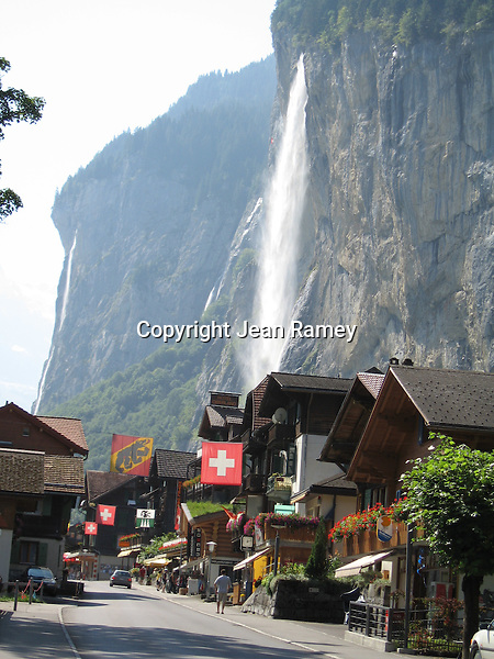 A mountain waterfall cascades over the Swiss Alps village of Lauderbrunnen