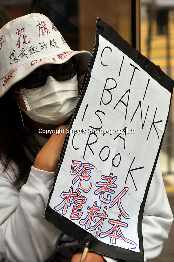 """Hong Kong investors demonstrate outside Citibank in Central District, Hong Kong. The demonstrators who lost much of their savings after Citi sold them financial products backed by Lehman denouncing Citi as a """"devil bank"""" that """"swindled us out of our life savings.""""."""