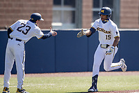 Michigan Wolverines outfielder Clark Elliott (15) celebrates with third base coach Nick Schnabel (23) after hitting his second home run during the NCAA baseball game against the Illinois Fighting Illini on March 20, 2021 at Fisher Stadium in Ann Arbor, Michigan. Michigan won the game 8-1. (Andrew Woolley/Four Seam Images)
