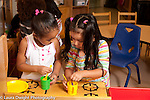 Education preschool first days of school two girls playing and interaction in pretend play area