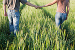 Russia, Voronezh, couple walking through field