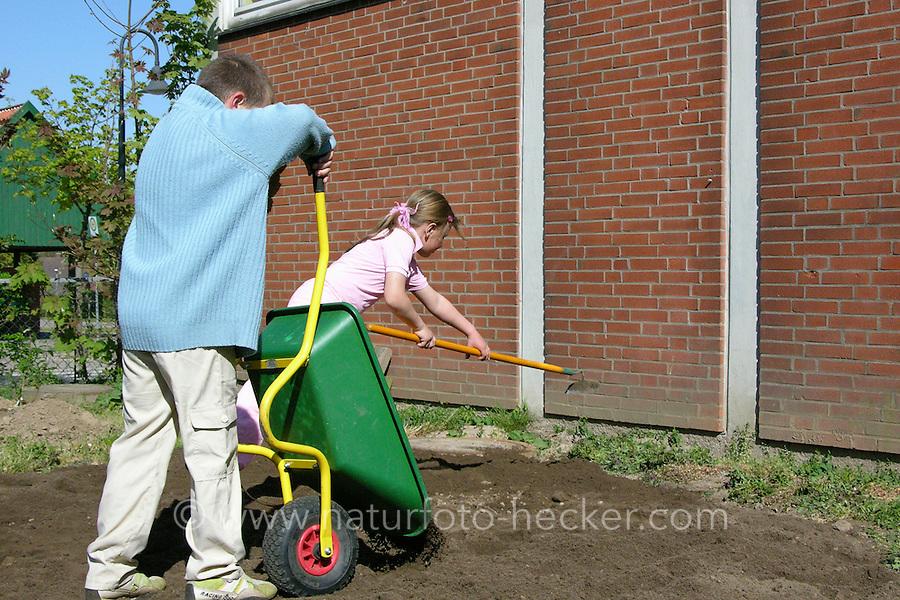 Schulgarten, Fläche am Schulgebäude, auf der ein Schmetterlingsgarten angelegt werden soll, Garten der Grundschule Nusse wird als Projektarbeit von einer 1. Klasse gestaltet, Kinder füllen Mutterboden zur Bodenverbesserung auf, Gartenarbeit