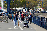 Pictured: People enjoy the sunny weather walking on Mumbles promenade near Swansea, Wales, UK. Monday 26 April 2021<br /> Re: Lockdown rules caused by the Covid-19 Coronavirus pandemic have been relaxed, with outdoors pubs, restaurants and cafes now open in Wales, UK.