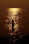Zanzibar, Tanzania. Person swimming in the sea as the sun goes down.
