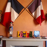 Detail of a mantelpiece where a toy soldier stands to attention beneath a pair of crossed French flags