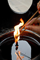Lighting incense sticks at an oil lamp at the Wenshu Temple, Chengdu,China.