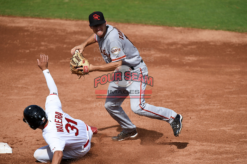 Scottsdale Scorpions infielder Kelby Tomlinson (18) turns a double play as Breyvic Valera (31) slides in during an Arizona Fall League game against the Peoria Javelinas on October 18, 2014 at Surprise Stadium in Surprise, Arizona.  Peoria defeated Scottsdale 4-3.  (Mike Janes/Four Seam Images)