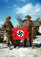 These two Canadian soldiers raise a Nazi flag which they captured in France,	<br /> <br /> ca summer 1944<br /> Author 	<br /> <br /> credited to National Archives of Canada
