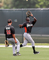 Miami Marlins outfielder Juancito Martinez #84 catches a fly ball as Jhiomar Veras #92 looks on during an extended Spring Training game against the New York Mets at the Roger Deam Complex on May 1, 2012 in Jupiter, Florida.  (Mike Janes/Four Seam Images)
