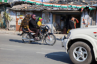India, Dehradun.  Family on a Motorbike--Helmet for the Man, none for the woman or boy.