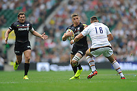 Owen Farrell of Saracens looks to hand off Tom Lindsay of Wasps during the Premiership Rugby Round 1 match between Saracens and Wasps at Twickenham Stadium on Saturday 6th September 2014 (Photo by Rob Munro)