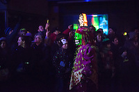 A masked carnival participant walks by a crowd of onlookers during 'Morgenstreich', when about 200 lanterns are carried by 'cliques' through a completely dark old town of Basel, moments after the official start of the 2015 Fasnacht, Carnival of Basel in Switzerland. Feb. 23, 2015.