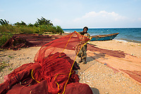 """Ishimalanga with her fishing nets, Lake Tanganyika, Congo.<br /> Statistics show that a woman is raped every minute in the Congo. These atrocious attacks are considered an on-going """"weapon of war"""" committed by rebels and even local police and militants. The women and young girls in these areas find themselves most vulnerable when simply performing the necessary but isolating chore of gathering wood and water in the forest for their families. Often they become impregnated and are then abandoned by their husbands and family.<br /> Ishimalanga Nabugamba suffered physical abuse, lost most of her family members and all her property during the war. An international program has helped train thousands of women in work skills programs to help regain their dignity through financial stability and a sense of community with micro-loans and the merry-go-round program where women pool their money together and take turns receiving the pot at the end of the month. <br /> Ishimalanga, shown here with her fishing boat on Lake Tanganyika where she learned to fish, bought a large fishing net with her proceeds. She hopes she can pass this skill on to her children and now has a sense of purpose and hope in her life."""