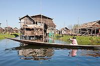 Myanmar, Burma.  Village Scene, Woman Rowing Boat, Houses on Stilts, Inle Lake, Shan State.