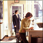 Woman standing by counter in cafe with man coming through door in background