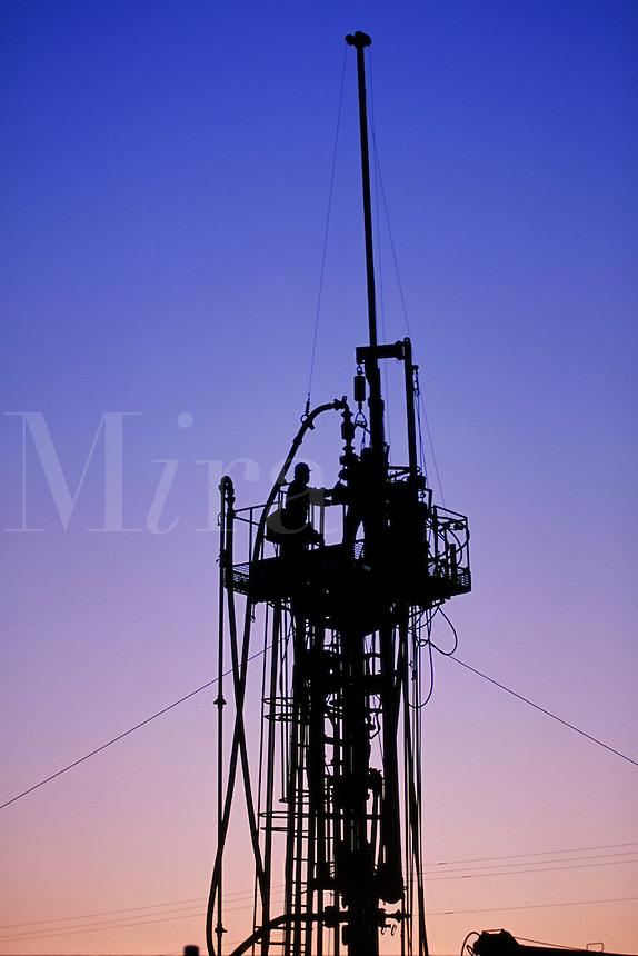 workers on oil rig platform at sunrise
