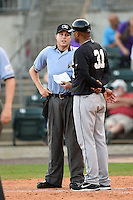 Umpire Matthew Czajak explains a call to San Antonio Missions hitting coach Francisco Morales (31) during a game against the Arkansas Travelers on May 25, 2014 at Dickey-Stephens Park in Little Rock, Arkansas.  Arkansas defeated San Antonio 3-1.  (Mike Janes/Four Seam Images)