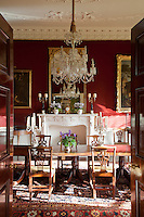 A lavish red dining room with white stucco decoration on the ceiling, cornice and carved ribbons on the fire surround