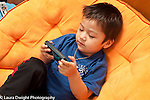 3 year old boy playing electronic game on cell telephone