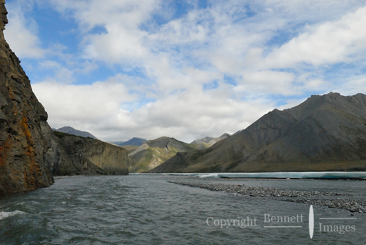 The multicolored mountains of the Brooks Range rise above aufeis along the Kongakut River, in Alaska's Arctic National Wildlife Refuge.