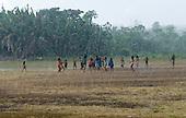 Pará State, Brazil. Aldeia Apyterewa (Parakana). Children playing ball in the rain.