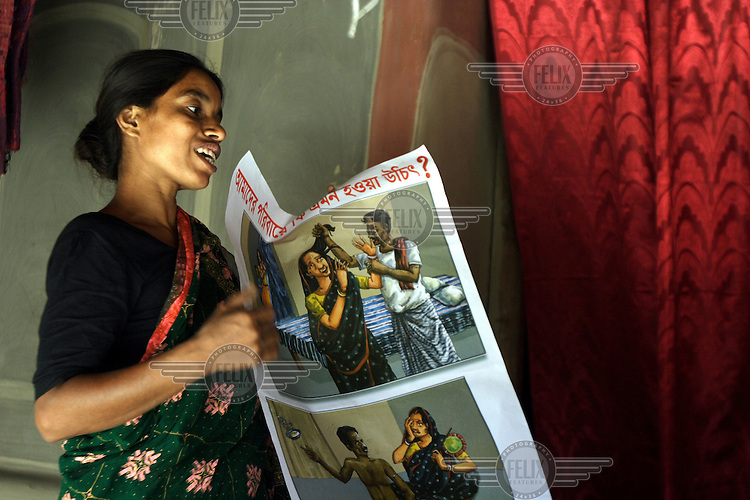 Change Maker and seamstress, Beauty Ara makes a presentation using posters that depict domestic violence to the committee on domestic violence in the village of Dinajpur. When Beauty was married her husband tortured her, he then divorced her and she lost the custody of her children. She did not give up, rather, having taken a loan, she purchased a sewing machine with which she now earns enough to stand on her own feet. However, she has not forgotten the misery of her troubled marriage. Now she goes from house to house, and wherever she finds married couples having marital problems, she assists them in understanding and solving their difficulties and in doing so advocates strongly for women's rights. .'We Can (end all violence against women)' is a grassroots campaign of ordinary men and women across South Asia who are seeking to find solutions to violence in their homes and lives, and find ways to reject it. Central to the campaign are the Change Makers, people actively committing to not perpetuating or supporting violence and influencing others to take a similar path. .