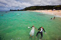 Couple enjoying the blue waters of Waimea Bay in their wedding attire