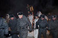 Moscow, Russia, 19/01/2010..Police use their batons to form a cordon around a procession during overnight Orthodox Epiphany celebrations. Russian priests and Orthodox believers celebrated Epiphany at Svyatoye Ozero, or Holy Lake, in Moscow's eastern Kosino district. Priests blessed the waters and followers baptised themselves by total immersion in the freezing lake in temperatures of minus 24C.