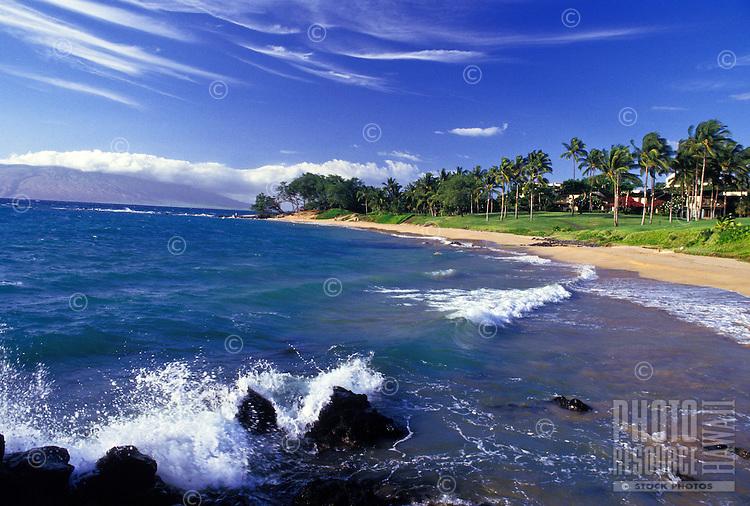Maui's beautiful Wailea beach beneath a bright blue sky streaked with clouds.