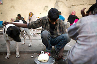 A homeless man with a stray dog by the side of the road at a temporary shelter in Karol Bagh, New Delhi.