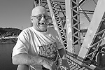 A bald man standing on a bridge wearing a Nascar shirt laughing with missing front teeth