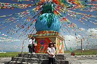 Tourists pose for photos next to a Tibetan stupa on the Qinghai-Tibetan Plateau. Qinghai Province. China. 2010