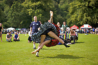 Men wearing kilts compete in the backhold wrestling event at the Inveraray Highland Games, held at Inveraray Castle in Argyll.