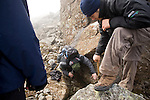 Robert Way watchs as a fellow student pours water on rocks searching for striations to determine if the glacier was warm or cold, moving or stationary.