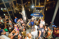 Spectators pose with a Pacific Blue marlin grander at Honokohau Harbor, Kailua-Kona, Big Island.
